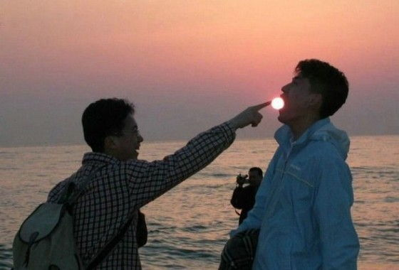 Asian guy stuffs a sun into the mouth of another person