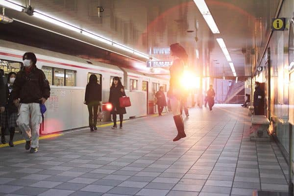 pretty japanese girl floats in front of train