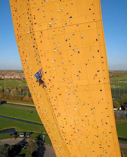 man climbing largest climbing wall
