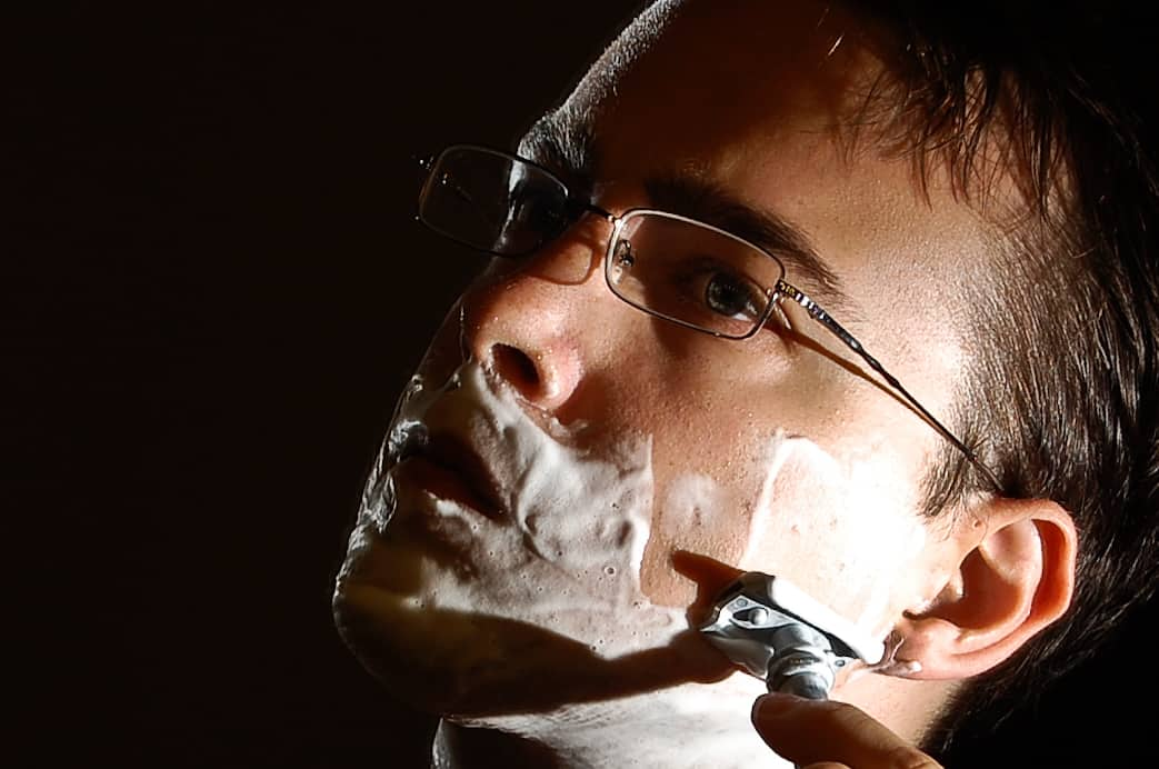 man-shaving-face-with-glasses